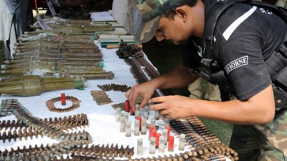 A policeman September 1 in Peshawar displays ammunition and explosives that police seized in a major operation. Police made 87 arrests in that operation. [Javed Khan]
