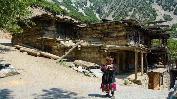 A Kalash girl stands near her house in the Kalash Valley, Chitral District, in August. [Alamgir Khan]