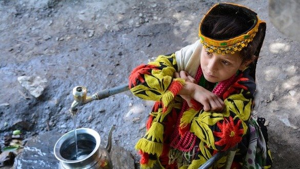 A Kalash girl fills a container with spring water. [Alamgir Khan]