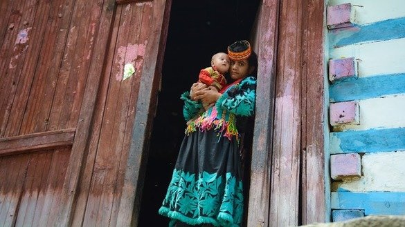 A Kalash woman stands with her baby in her doorway. [Alamgir Khan]