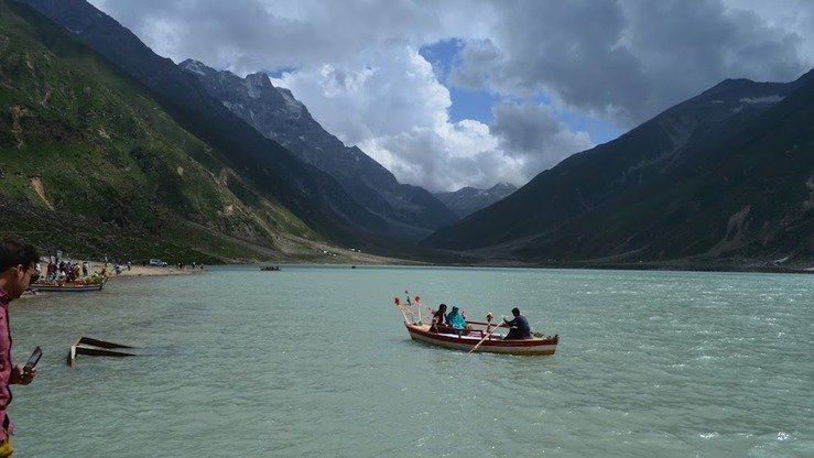Tourists take a boat ride on Lake Saiful Muluk in August. [Qasim Yousafzai]