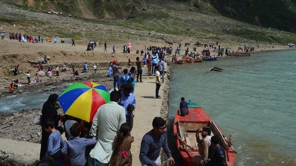 Tourists from across the country view Lake Saiful Muluk and take photos in August. [Qasim Yousafzai]