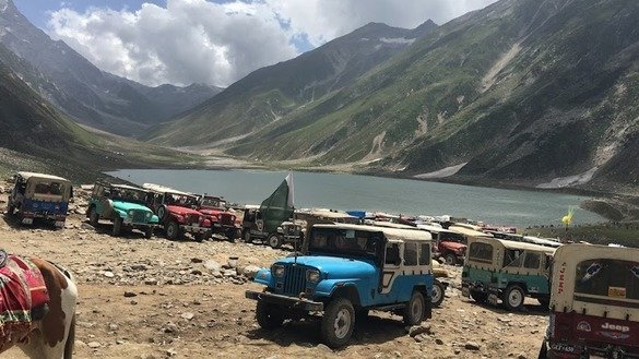 Jeeps are shown parked on the side of Lake Saiful Muluk. Jeeps are the only way to reach the area because of rough, rocky roads. [Qasim Yousafzai]