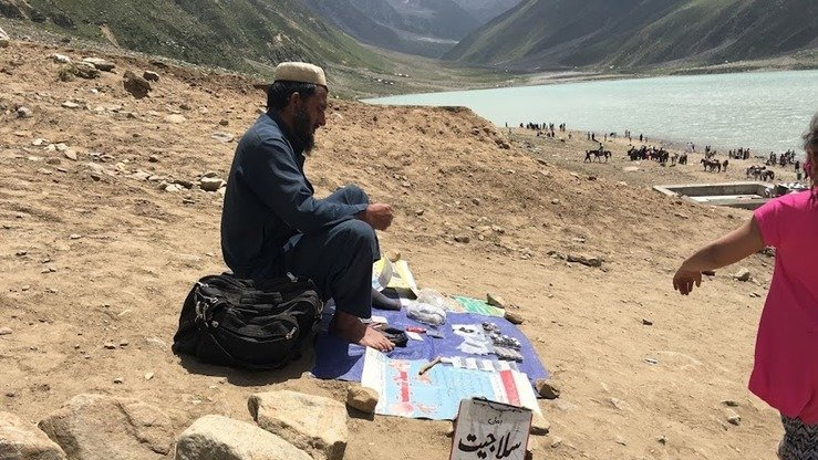 "A local vendor sells locally made health tonic called ""salajeed"" at Lake Saiful Muluk in August. [Qasim Yousafzai]"
