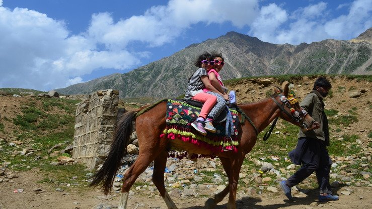 Children ride horseback near Lake Saiful Muluk in Naran Valley in August. [Qasim Yousafzai]