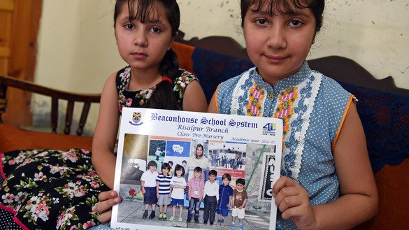 Warisha (right) and Zofisha, sisters of Noeen -- who was killed in June by a stray bullet of celebratory gunfire after Pakistan defeated arch-rival India in cricket -- on July 24 in Nowshera, Khyber Pakhtunkhwa, hold a school photo of him. [Abdul Majeed/AFP]