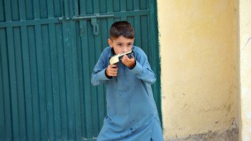 A Pakistani boy holds a toy gun in Islamabad August 20, 2012. The government is working to reform Pakistan's deeply rooted gun culture. [Aamir Qureshi/AFP]