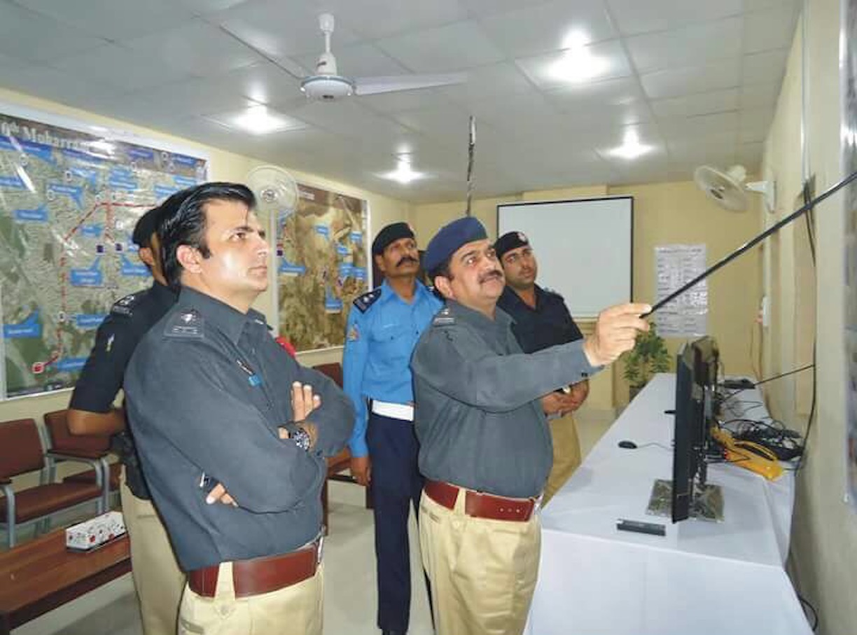 A police officer September 18 at a special command post for monitoring security during Ashura briefs Kohat District Police Officer Javed Iqbal (arms folded) about security arrangements made for the holy month of Muharram. [Kohat Police]
