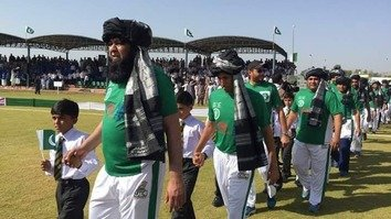 Former Pakistani cricket team captain Inzimam ul Haq, wearing a tribal turban, leads cricket players into a stadium in Miranshah September 25. [Courtesy of ISPR]