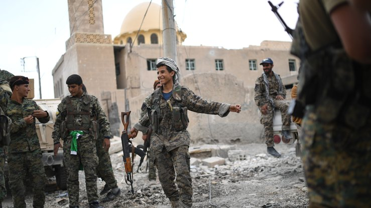 Members of the Syrian Democratic Forces dance as they hold a position on the eastern front line of Raqqa September 24. Syrian fighters backed by coalition forces are battling to clear the last remaining ISIS members holed up in their crumbling stronghold of Raqqa. [Bulent Kilic/AFP]