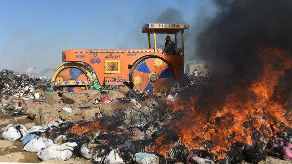 Pakistani customs officials crush liquor bottles with a steamroller on the outskirts of Karachi January 26. Officials destroyed smuggled drugs and alcohol on International Customs Day. [Asif Hassan/AFP]