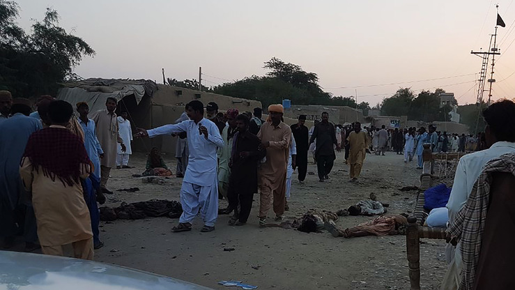 Pakistani devotees gather around the bodies of blast victims after a suicide bombing near a sufi shrine in the Gandawa area of Jhal Magsi district on October 5, 2017. [STR/AFP]