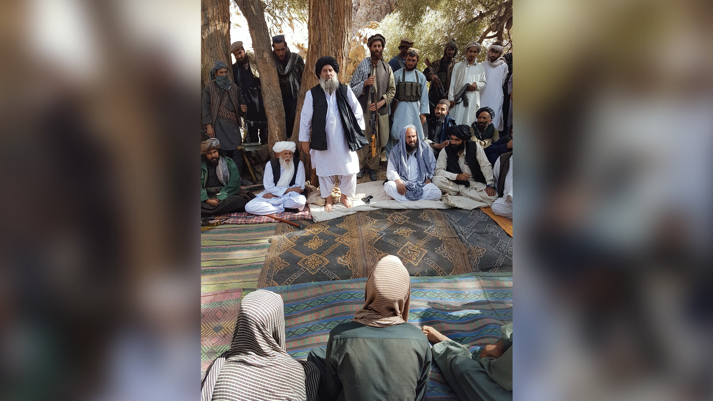 Three captured would-be suicide bombers sit in front of Mullah Manan Niazi as he speaks to his followers in an undated photo. [Courtesy of Mullah Manan Niazi]