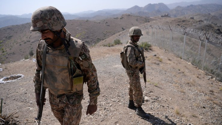 Pakistani soldiers patrol next to a newly fenced border separating North Waziristan and Afghanistan October 18. [Aamir Qureshi/AFP]