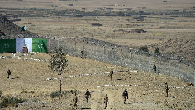 Pakistani soldiers patrol next to a new fence separating Angoor Adda, South Waziristan, and Paktika Province, Afghanistan, October 18. [Aamir Qureshi/AFP]
