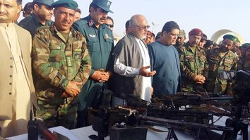 Farah Province officials in an undated photo show weapons that troops seized from the Taliban during September 28 operations in the province. [Farah governor's press office].