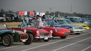A Pakistani photographs vintage cars during the Pakistan Motor Rally in Islamabad October 23. [Farooq Naeem/AFP]