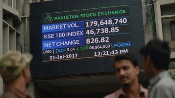 Stockbrokers watch the latest share prices at the Pakistan Stock Exchange (PSX) in Karachi July 31. [Rizwan Tabassum/AFP]