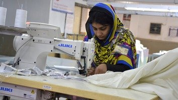 In this photograph last November 16, a Pakistani seamstress works at a textile factory in Faisalabad. [Khalil Ur-Rehman/AFP]