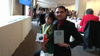 Esa, age 5, is shown with his father, Mukhtar Zaheer, after winning first prize for his age category at the Peace in the Streets Global Film Festival in New York November 9. [Courtesy of the Zaheer family]