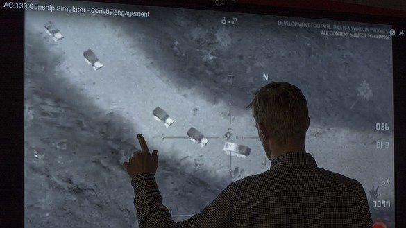 A journalist in Washington, DC, November 14 looks at YouTube video showing images from a aerial assault video game. Russia's Defence Ministry shared the same footage online, saying it proved the United States was aiding ISIS in the Middle East, but social media users pointed out the misinformation. [STF/AFP]