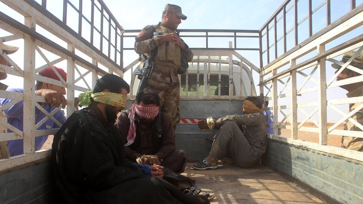 Iraqi pro-government forces detain men suspected of belonging to ISIS during their offensive against the jihadists to recapture the town of Rawa, on the Euphrates river, on October 28, 2017. [MOADH AL-DULAIMI / AFP]