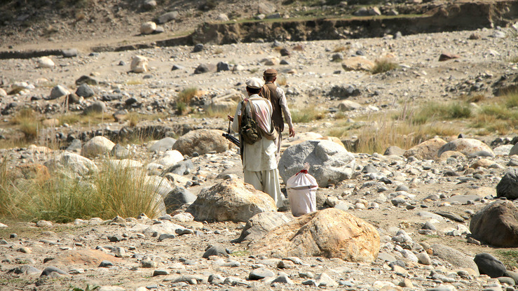 Two armed men, reported to be Taliban insurgents, flee the area after fighting with ISIS members in Khogyani District, Nangarhar Province, on October 17. Recent clashes between ISIS and the Taliban have forced hundreds of civilians to flee their homes as well. [Khalid Zerai]