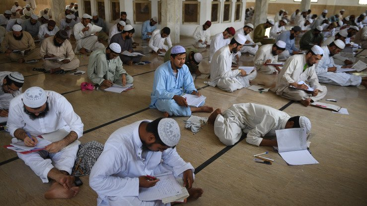 Seminary students sit for an exam at Jamia Binoria, Pakistan's largest Islamic seminary, in Karachi April 30. [Asif Hassan/AFP]