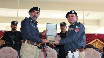 Elite Force Commandant Dr. Muhammad Naeem Khan (right) presents the police shield to KP Inspector General of Police Salahuddin Khan Mehsud during the graduation ceremony of the Operational Command Course at the Elite Police Training Centre in Nowshera October 19. [KP Police]