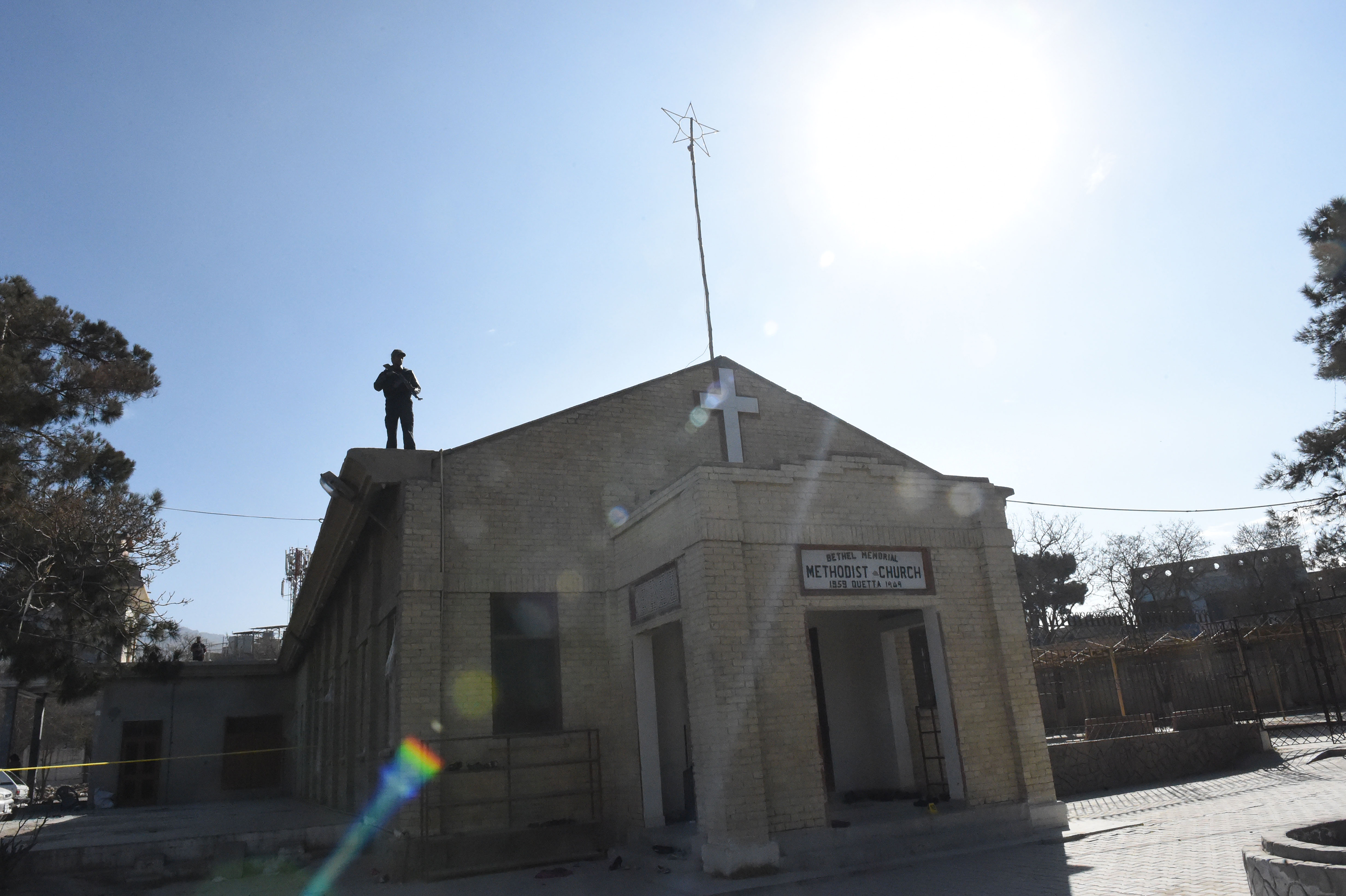 A policeman December 18 stands guard on the roof of Bethel Memorial Methodist Church in Quetta, a day after an ISIS suicide bombing that targeted the church. [Banaras Khan/AFP]