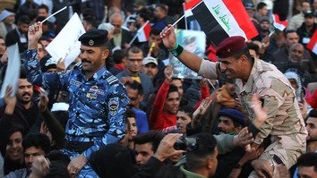 An Iraqi soldier and policeman wave their national flag in Tahrir Square, Baghdad, December 10 during a celebration of victory in the three-year-long war against IS. [Ahmad Al-Rubaye/AFP]