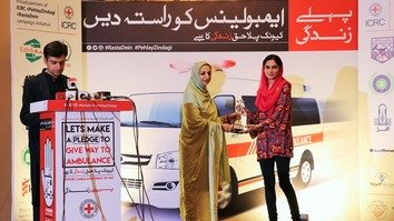 "Minister of State for National Health Services Regulation and Co-ordination Saira Afzal Tarar (centre) presents an award to a participant during a ""Give Way to Ambulances"" campaign event in Islamabad in October. [International Committee of the Red Cross]"