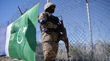 A Pakistani soldier keeps vigil next to a newly built fence in South Waziristan along the Afghan border October 18. The new fences and hundreds of forts will help curb mllitancy, says the Pakistani military. [Aamir Qureshi/AFP]