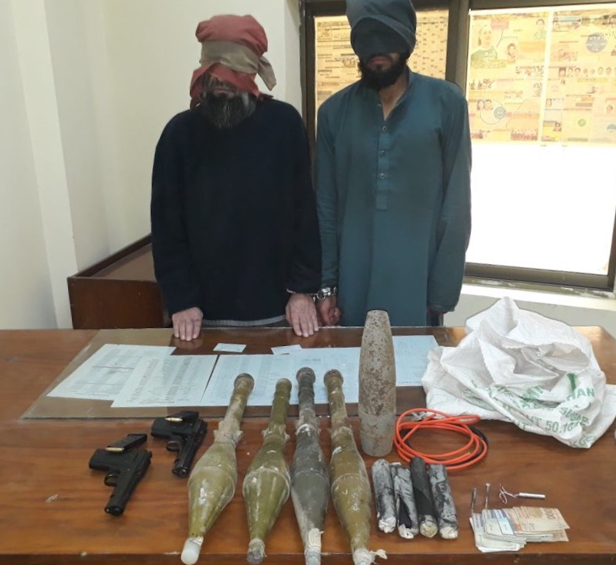 Two militants held by KP Police on December 29, 2017, pose with a number of seized explosives in Peshawar. [KP Police]