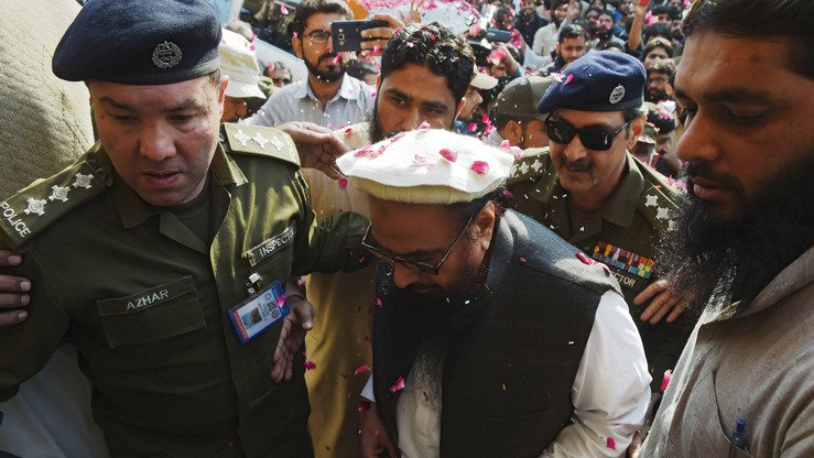Pakistani police officials escort Jamaat-ud-Dawa (JuD) chief Hafiz Saeed (centre) as he arrives at a court in Lahore last November 22. [Arif Ali/AFP]