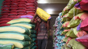 A Pakistani worker carries a sack of rice at the main wholesale market in Karachi last May 25. Indonesia is set to begin importing large quantities of Pakistani rice through private sector agreements. [Asif Hassan/AFP]