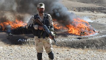 A Pakistani Anti Narcotics Force member stands in front of a pile of burning illegal drugs during a ceremony in Quetta December 12. More than 45% of Afghanistan's illicit opiates pass through Pakistan en route to markets in Europe and Asia, according to the UN Office on Drugs and Crime. Militants are largely responsible for the production of the drugs, despite claiming that their cause is Islamic. [Banaras Khan/AFP]