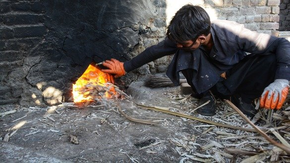 A farmer in Charsadda District fuels the fire of a traditional sugarcane mill in January. [Alamgir Khan]