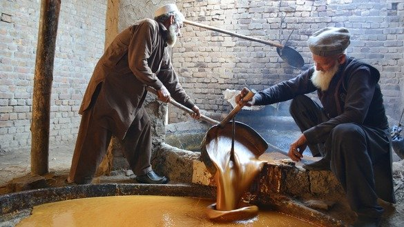Farmers transfer liquid gur from a cooking vessel to a processing vessel in Charsadda District in January. [Alamgir Khan]