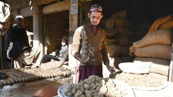 A store worker in Charsadda District in January sells gur. [Alamgir Khan]