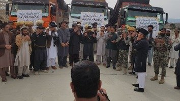 Officials, businessmen and locals offer prayers March 9 before the departure of a convoy of trucks to Afghanistan as part of the re-opening of the Ghulam Khan crossing in North Waziristan. [Asmat Shah]