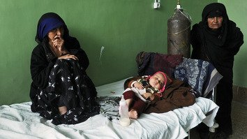 Afghan women look on as a child lies on a bed in the tuberculosis (TB) ward of the main hospital in Herat on April 9, 2012. At the time, the World Health Organisation estimated that more than 10,000 Afghans die annually from TB. [Aref Karimi/AFP]