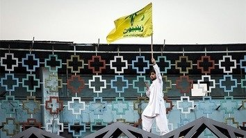 A Pakistani man waves the flag of the Zainabiyoun Brigade at an IRGC-sponsored event in Tehran in 2015. [Tasnim]