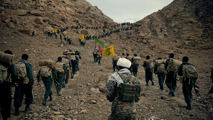 Members of the IRGC-backed Afghan Fatemiyoun Division march up a hill in this updated photo from Syria, where they are fighting, with the Russian military's help, to support Syrian President Bashar al-Assad and Iran's sectarian interests. [File]