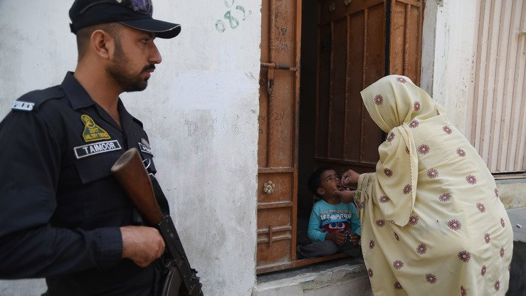 A Pakistani health worker administers polio vaccine drops to a child as a policeman stands guard in Karachi March 14. [Asif Hassan/AFP]