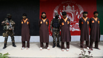 Afghan security forces stand next to five arrested Taliban suspects as they are presented to media in Ghazni Province April 14. [Zakeria Hashimi/AFP]