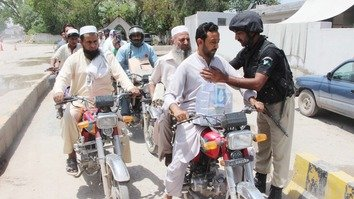 A policeman searches motorcyclists entering Peshawar on May 16, a day before the start of Ramadan. [Peshawar Police]