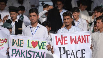 Pakistani spectators carry placards during a Twenty20 cricket match between Pakistan XI and UK Media XI in Miranshah, North Waziristan, a former stronghold of al-Qaeda and Taliban militants, last September 21. The National Assembly May 24 passed a bill approving the merger of FATA with KP. [Aamir Qureshi/AFP]