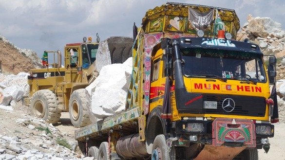 Workers load a truck with marble in Mohmand Agency in May. [Alamgir Khan]