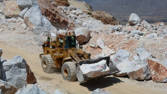A loader hauls marble to a nearby truck in Mohmand Agency in May. [Alamgir Khan]